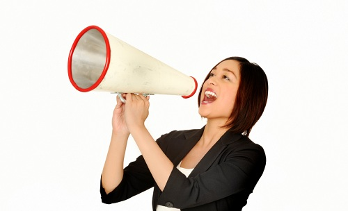 young professional woman making an announcement through a megaphone.